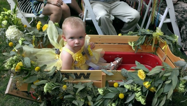 Granddaughter Magnolia in her Wagon and the dress I made.  With the heat, she wasn't very happy - but still extremely cute!